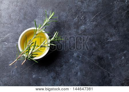 Herbs and spices. Cooking ingredients. Rosemary and olive oil. Top view over stone table with copy space for your recipe