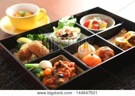 Bento of Temari sushi shrimp and marinated mushrooms egg grilled tomato spring vegetables beef and asparagus croquettes boiled tomato of Italian-style chicken