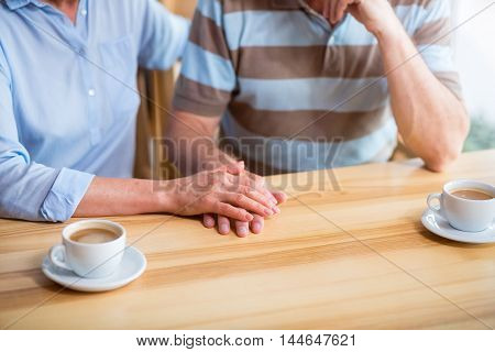 Forever together. Pleasant senior loving couple holding hands together and sitting at the table while resting in the cafe