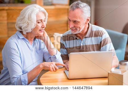 Here it is. Positive delighted senior couple sitting at the table and using laptop while resting together