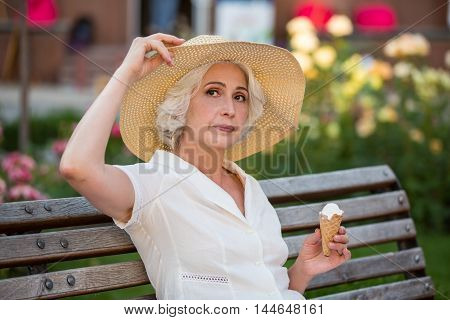 Mature lady with ice cream. Woman touching her hat. Spending summer in home city. Look to the side.