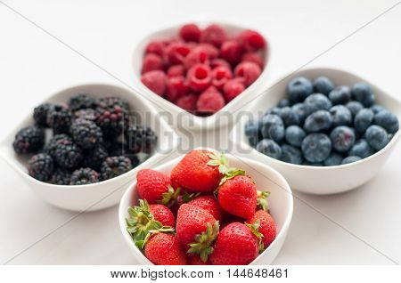 on a white background in white bowls of fresh, juicy wild berries blueberries raspberries strawberries and blackberries, delicious Supplement to any diet meals.