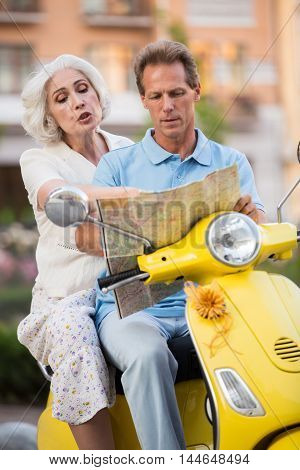 Mature people sitting on scooter. Man with map beside woman. We should turn here. I don't know this town.