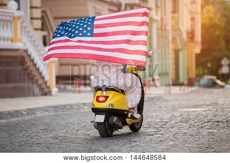 Couple is riding a scooter. Flag of US. Travelling around America. Free as a bird.