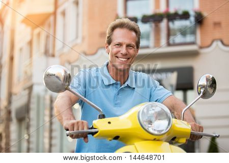 Adult man on scooter smiling. Guy in light blue t-shirt. Feeling happy after trip. Spend every day with joy.