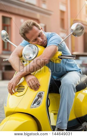 Man on scooter is sleeping. Tired guy on street background. Trip took much energy. Finally I can rest.