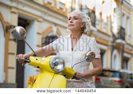 Woman holds scooter's steering wheel. Mature lady with confident face. I choose the right route. No obstacles during the trip.