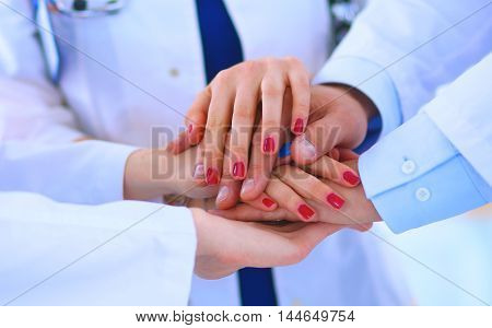 Doctors and nurses in a medical team stacking hands .