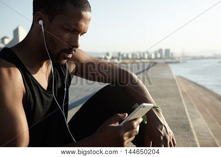 Handsome Dark-skinned Jogger Wearing Black Sleeveless Top Listening To Music With Headphones, Browsi