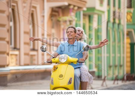 Couple is riding a scooter. Smiling man and woman. Value the time spent together. All ways are open.