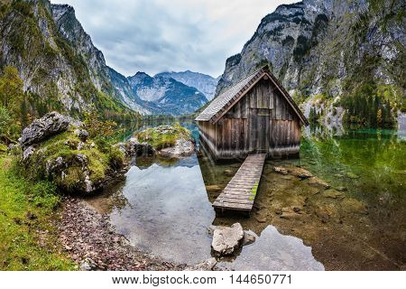 The concept of active tourism and ecotourism. Enchanted Lake Obersee in the Bavarian Alps. Boat garage in the middle of the lake