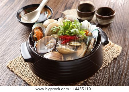 Black stew of Jogaetang clam soup with chili and cumin herbs on wooden korean table