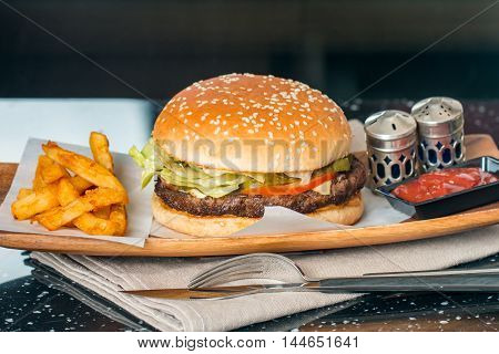 Cheeseburger on sesame buns with succulent beef patties and fresh salad ingredients on paper served  with French Fries and Beer on black table