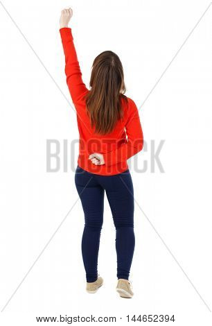 Back view of woman. Raised his fist up in victory sign. Isolated over white background. The girl in the red sweater happily raised his fist up.