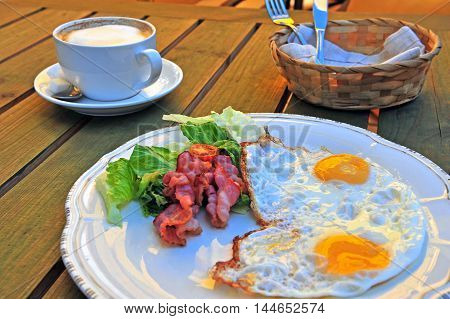 English breakfast on the wooden table: sunny side up eggs with bacon and vegetables