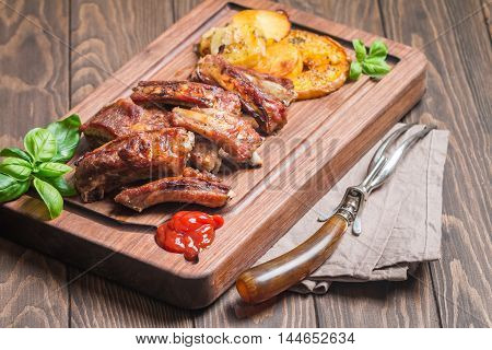 Delicious Grilled Pork Rib and Fried Potato Wedges with Sauce on wooden cutting board