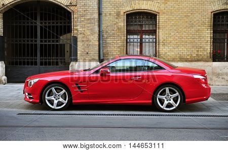 BUDAPEST - MAY 20 2016: Red Mercedes-Benz sport car in the street of Budapest on May 20 2016. Mercedes-Benz is a global automobile manufacturer founded in Germany.