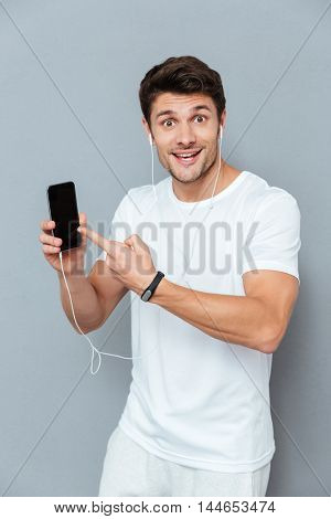 Cheerful young man with earphones pointing finger on smartphone with blank screen over gray background