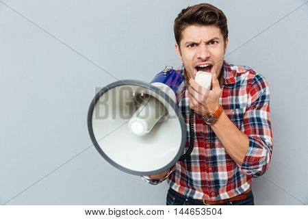 Mad crazy young man in plaid short shouting in megaphone over grey background