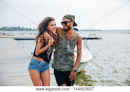 Portrait of romantic young beautiful couple in love standing at the wooden pier