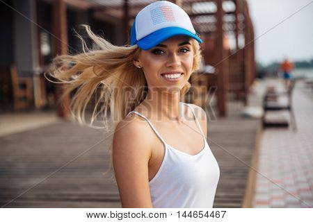 Cheerful pretty young woman in cap standing and smiling outdoors