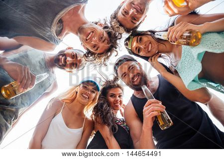 Low angle view of happy guys and girls standing together in a circle against blue sky and drinking beer