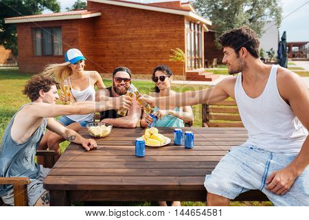 Group of happy young people with beer sitting and celebrating at the table outdoors