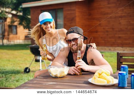 Cheerful beautiful young couple eating and drinking beer outdoors at the table