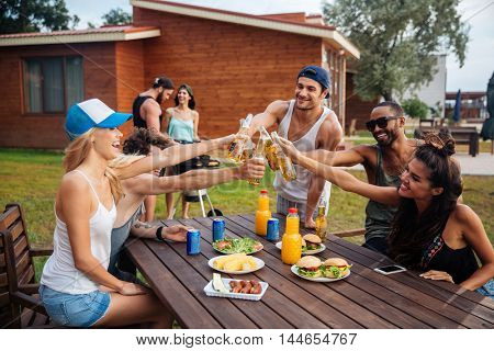 Group of cheerful young people celebrating and drinking beer on outdoor party