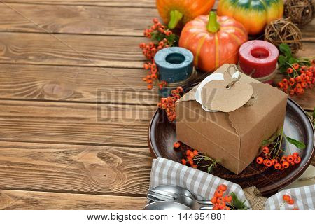Box and cutlery on brown background close up