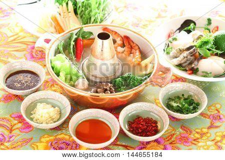Healthy creative Thai hot pot with shrimp mushroom broccoli onion garlic and lemon in big stew