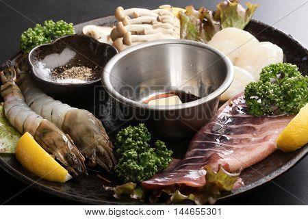Seafood hot pot with fresh raw shrimp squid scallop lemon cumin lettuce and mushroom on big black platter
