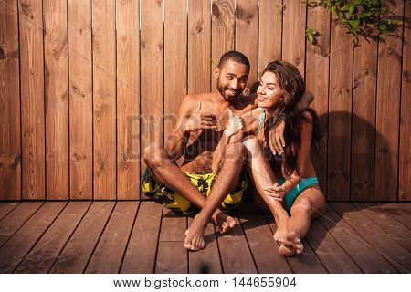 Lovely cheerful mixed race couple showing thumbs up over wooden background