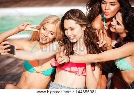 Four pretty young girls in bikinis making selfie with phone at the swimming pool