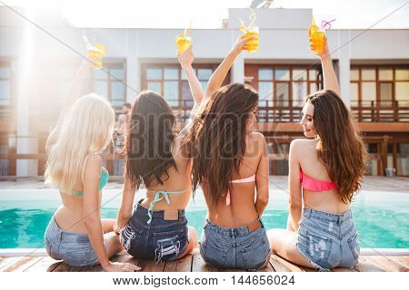 Back view of joyful young women drinking cocktails and having fun near swimming pool