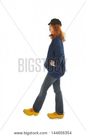 Funny female farmer from Holland walking by isolated over white background