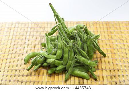 Fresh raw green soy bean on bamboo tray background