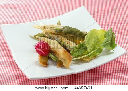 Tempura of shrimp meat with fresh red radish and cabbage on white platter
