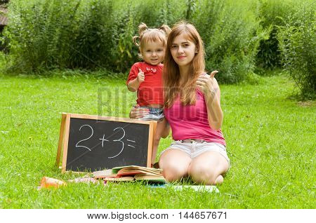 Mom and daughter are preparing for school and having fun in nature. They give thumps up