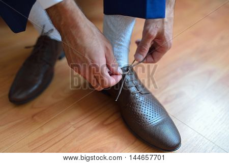 Businessman or groom tie a shoelace on his brown shoes. Shallow depth of field.