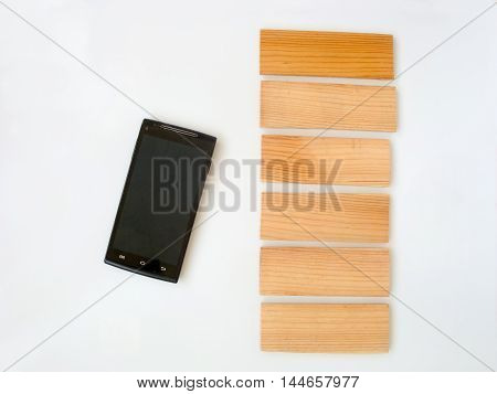 Phone on a white background. Near the wooden plank. White background can be any color and on tablets place my text.