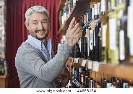 Mature Customer Choosing Wine Bottle In Store