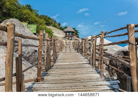 Wooden bridge on a rocky beach in Thailand