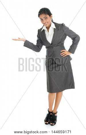 Full length portrait of Indian businesswoman hand showing something, standing isolated on white background.