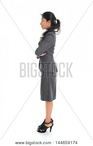 Full length side view of Indian businesswoman standing arms crossed isolated on white background.