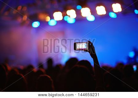 Back lit image of crowd at music concert before stage, focus on one fan holding cellphone high above heads to take picture of memorable moment