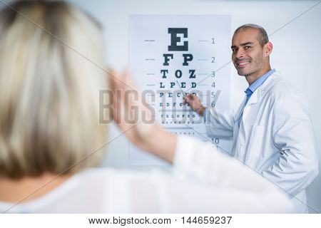 Male optometrist taking eye test of female patient in ophthalmology clinic