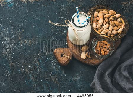 Fresh almond milk in glass bottle with almonds in bowls for healthy, raw and vegan diet on rustic wooden board over dark grunge plywood background. Top view, selective focus, copy space