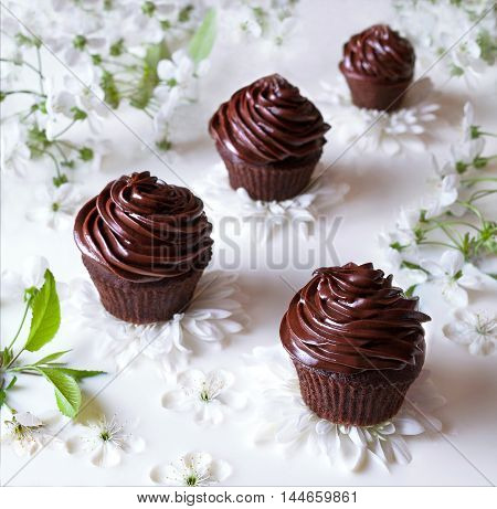 Delicious chocolate cupcakes with butter cream on a background of milk and flowers. Homemade pastries from organic natural products.