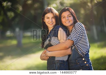 two beautiful young adult sisters hugging and smiling looking at the camera